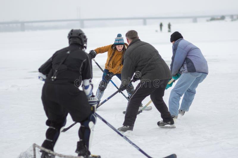 Ragazza coraggiosa del neenager che attacca piccolo scopo che uomini maturi che difendono mentre giocando hockey fotografia stock libera da diritti