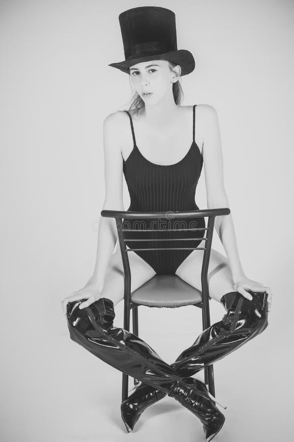 Ragazza in costume da bagno, in cappello ed in stivali alla moda neri sulla sedia fotografie stock
