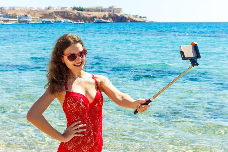 Ragazza in costume da bagno con uno Smart Phone sulla spiaggia Ragazza che prende il selfie di divertimento alla spiaggia fotografie stock