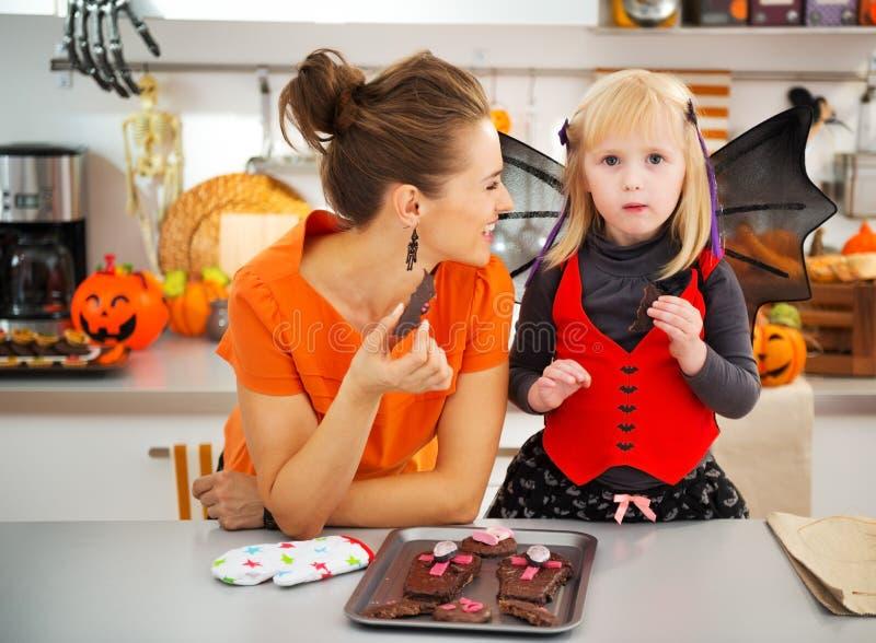 Ragazza in costume del pipistrello con la madre che mangia i biscotti di Halloween fotografia stock libera da diritti