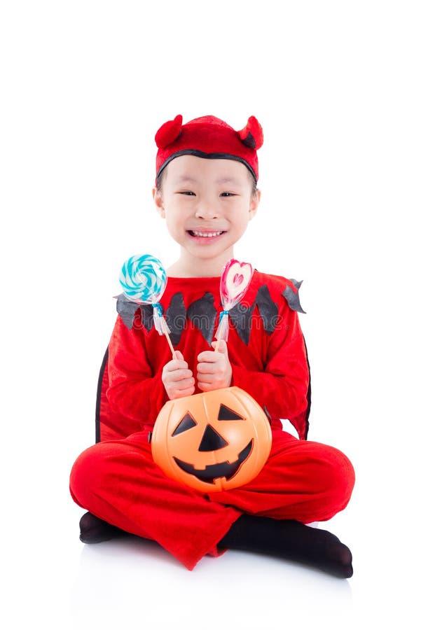 Ragazza in costume di Halloween del diavolo che si siede sopra il bianco immagini stock libere da diritti