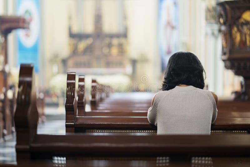 Ragazza cristiana che prega nella chiesa immagine stock libera da diritti
