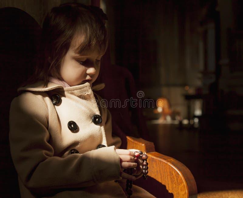 Ragazza cristiana del bambino che prega il rosario fede, concetto di religione fotografie stock