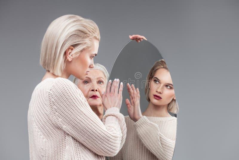 Ragazza curiosa bionda dai capelli corti in maglione tricottato che tocca superficie dello specchio fotografia stock