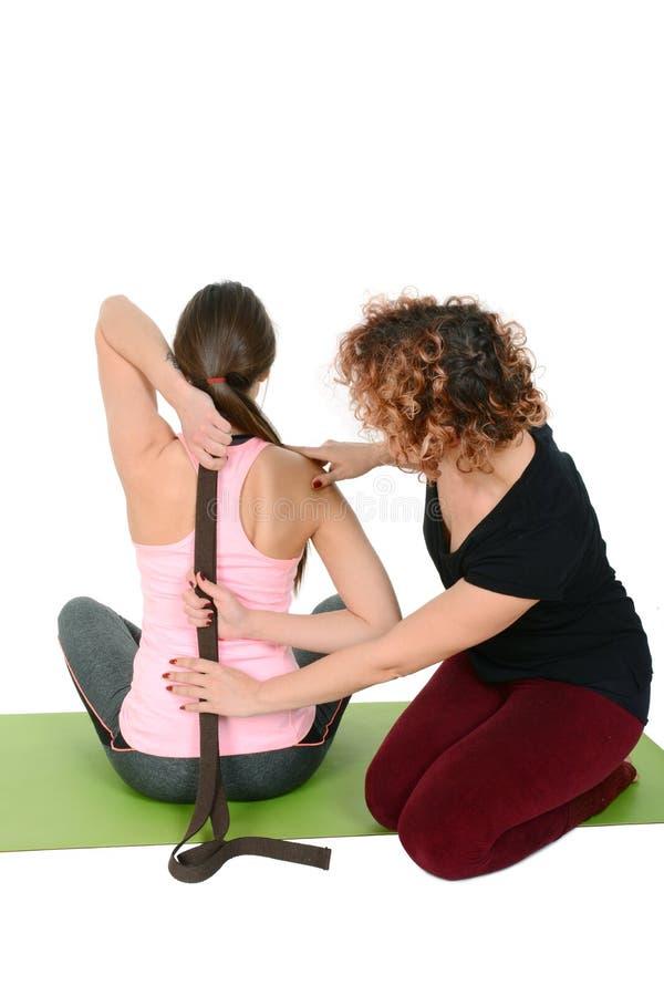 Ragazza d'aiuto dell'insegnante di yoga per fare yoga fotografie stock libere da diritti