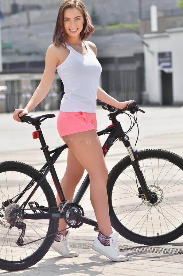 Ragazza d'avanguardia dei pantaloni a vita bassa con la bici su fondo urbano Foto tonificata e filtrata fotografia stock