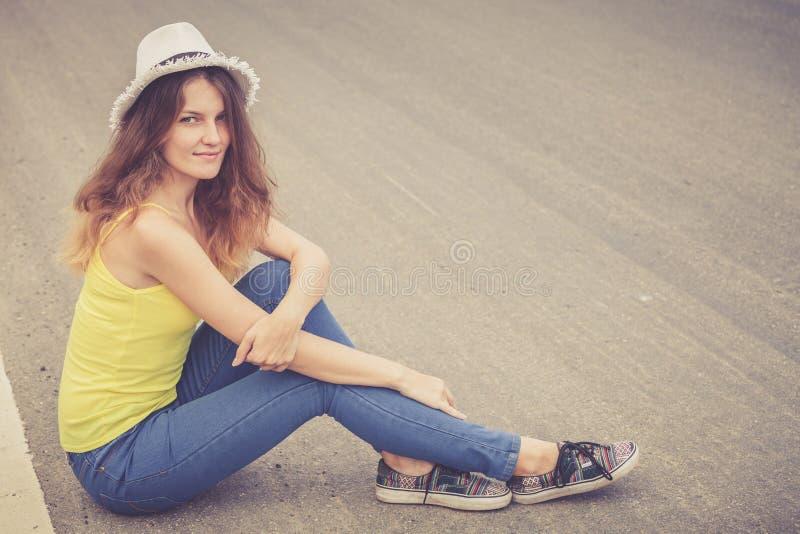 Ragazza d'avanguardia dei pantaloni a vita bassa nel cappello che si rilassa sulla strada al giorno t immagine stock