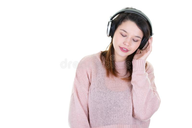 Ragazza dai capelli di Brown con le cuffie che ascolta la musica con gli occhi chiusi su fondo bianco con da parte lo spazio dell fotografia stock libera da diritti