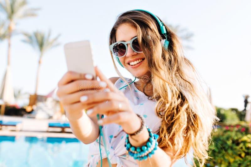 Ragazza dai capelli lunghi sorridente in occhiali da sole e cuffie che fanno foto di bello paesaggio con le palme esotiche allegr fotografia stock