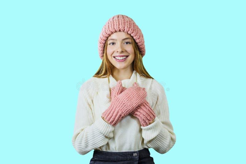 Ragazza dai capelli rossi attraente in cappello caldo e guanti che esaminano la macchina fotografica contro un fondo rosa isolato immagini stock