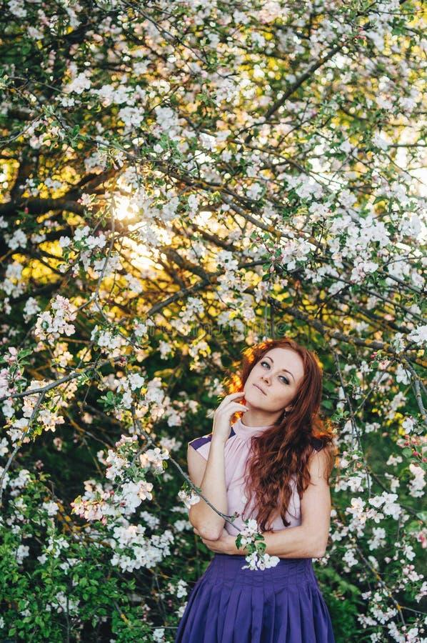 Ragazza dai capelli rossi con le lentiggini vicino di melo fotografie stock libere da diritti