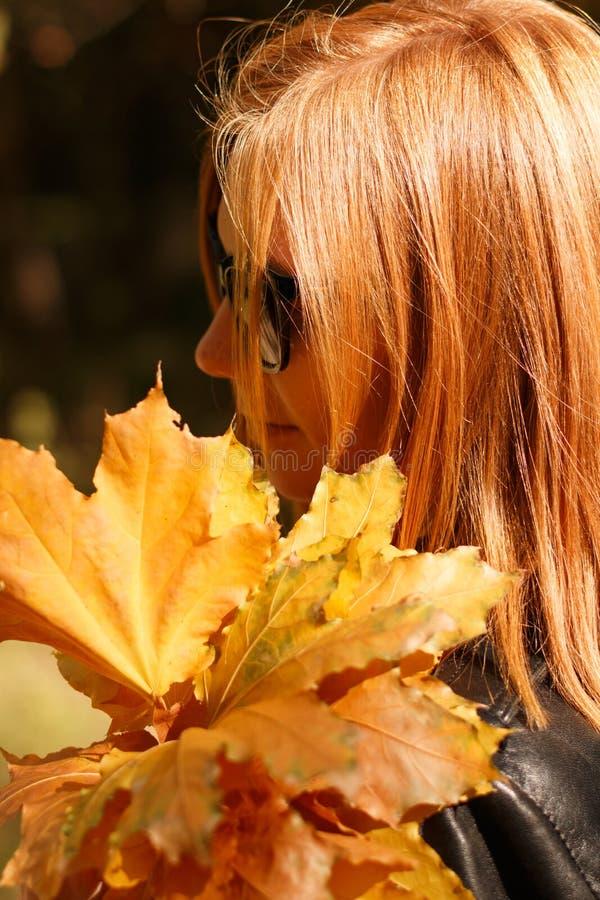 Ragazza dai capelli rossi in foglie di giallo delle tenute di vetro immagine stock libera da diritti