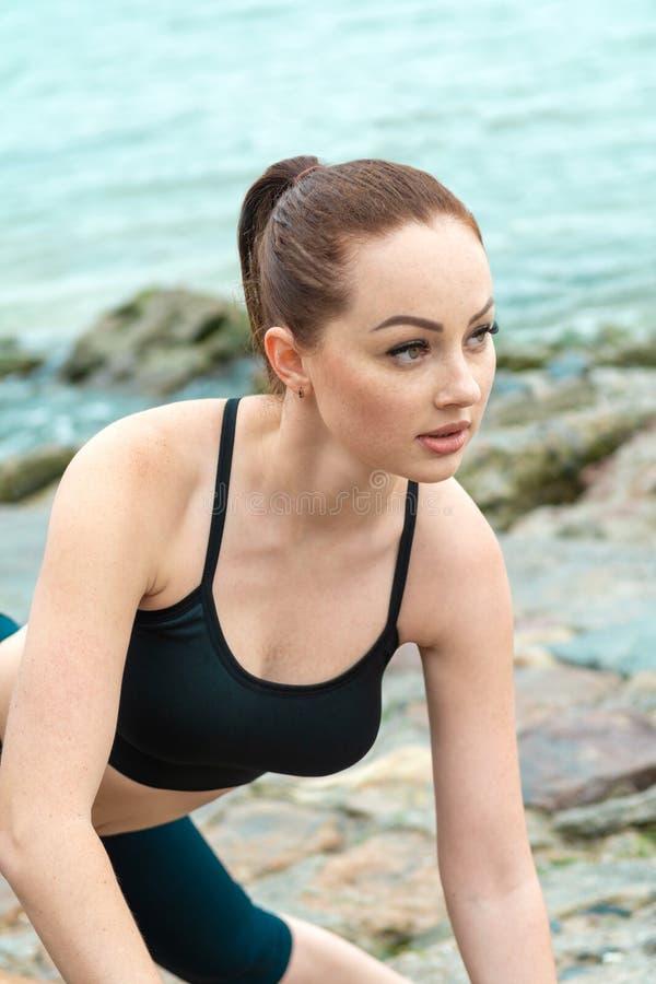 Ragazza dai capelli rossi, giovane, atletica, bella impegnata in ginnastica, funzionamento all'aperto Si esercita di sport per fotografia stock