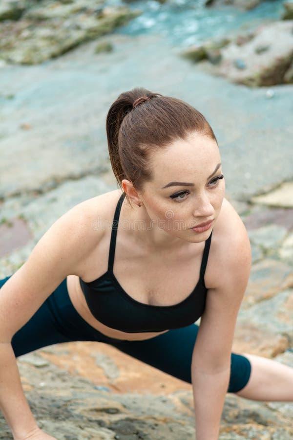 Ragazza dai capelli rossi, giovane, atletica, bella impegnata in ginnastica, funzionamento all'aperto Si esercita di sport per immagini stock libere da diritti