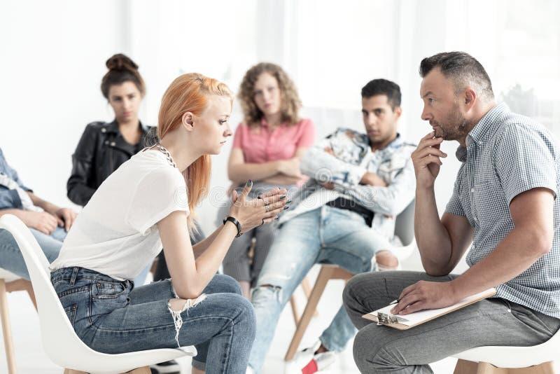 Ragazza dai capelli rossi ribelle che parla con consulente durante il meeti immagini stock