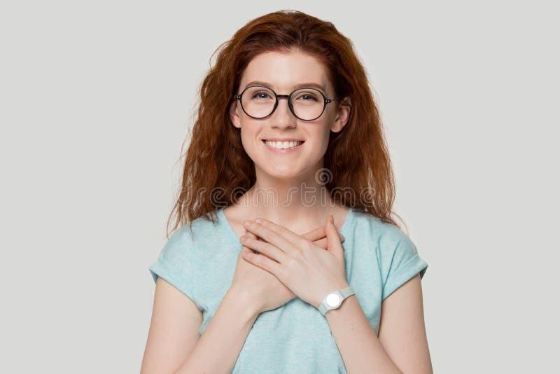 Ragazza dai capelli rossi riconoscente sorridente in vetri con le mani al petto fotografia stock