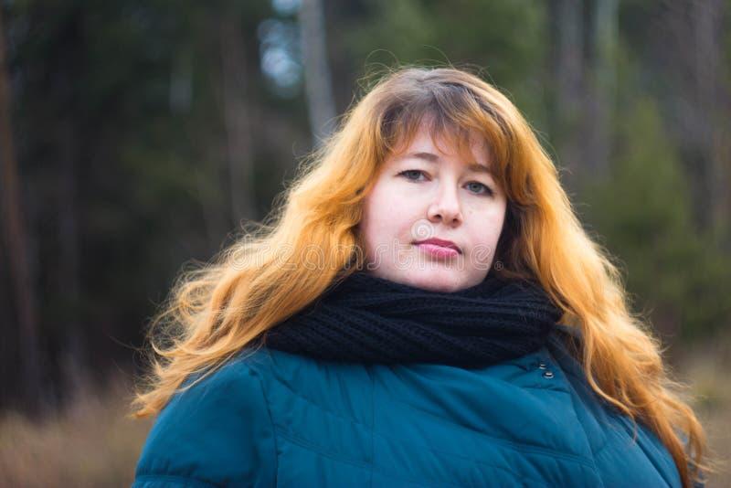 Ragazza dai capelli rossi in un rivestimento verde sulla via fotografie stock