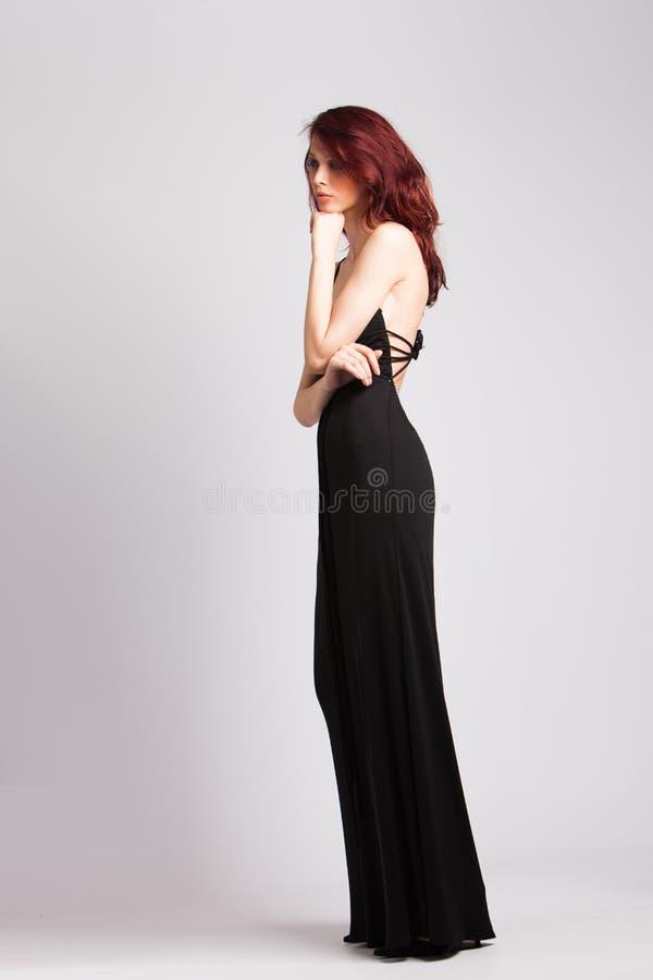 Ragazza dai capelli rossi in vestito da sera nero lungo immagini stock libere da diritti