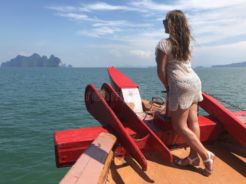 Ragazza dalla carnagione chiara in vestiti della spiaggia a bordo della nave un giorno di estate caldo contro il mare delle isole immagine stock