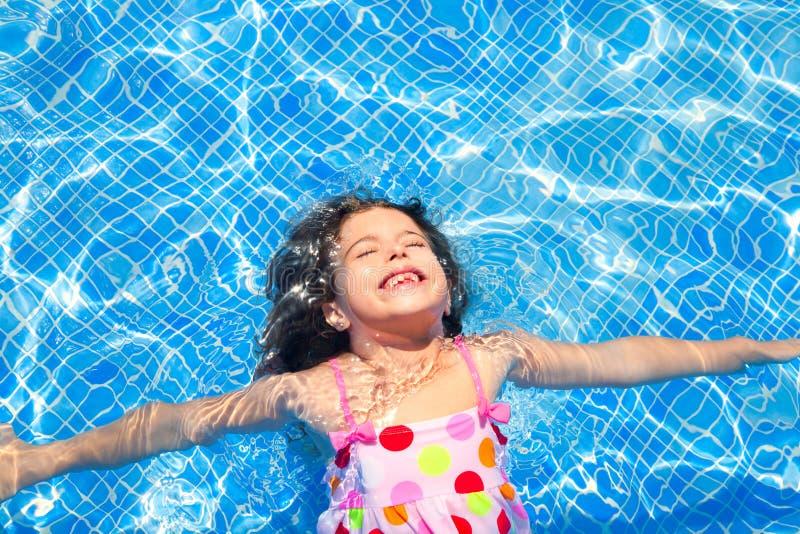 Ragazza dei bambini del Brunette che nuota il raggruppamento blu delle mattonelle fotografia stock libera da diritti