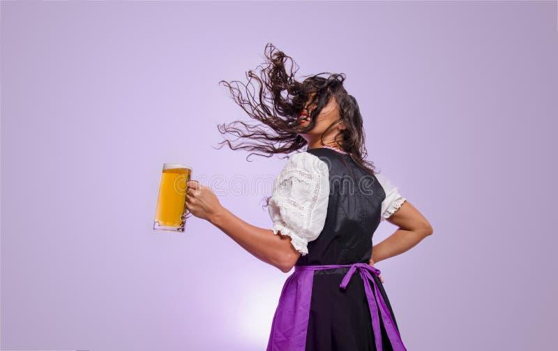 Ragazza dei capelli ricci, capelli di lancio e tenere la tazza di birra fotografia stock libera da diritti