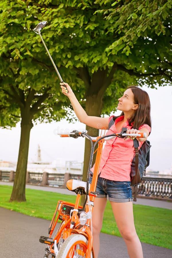 Ragazza dei pantaloni a vita bassa che fa selfie con la bici elettrica contro la città verde immagine stock libera da diritti