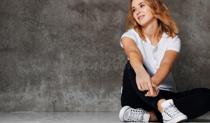 Ragazza dei pantaloni a vita bassa che porta maglietta bianca in bianco, jeans contro la parete, immagine stock