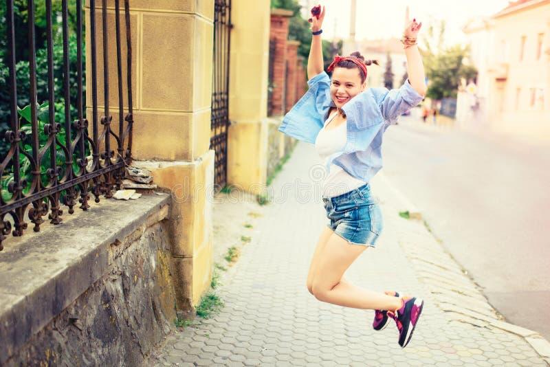 Ragazza dei pantaloni a vita bassa che salta intorno al paesaggio urbano durante il festival di musica Ragazza sorridente che son fotografie stock