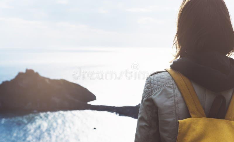 Ragazza dei pantaloni a vita bassa con lo zaino che gode del tramonto su vista sul mare sulla montagna di punta Il viaggiatore tu immagini stock