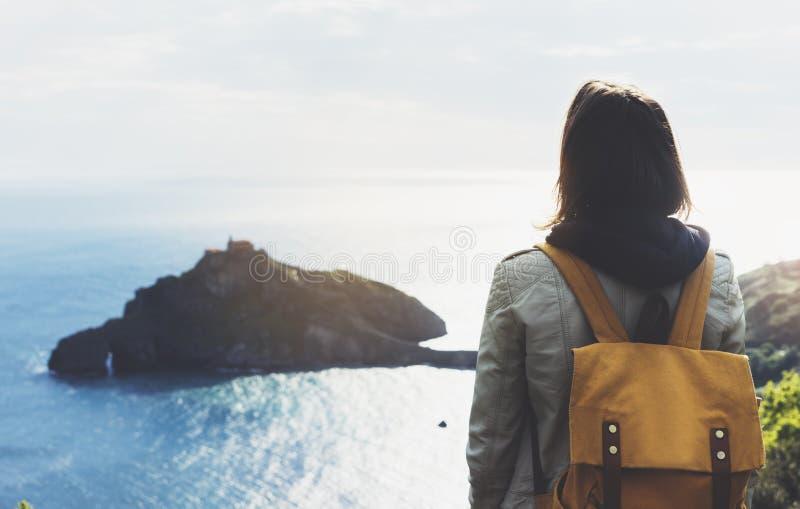 Ragazza dei pantaloni a vita bassa con lo zaino che gode del tramonto su vista sul mare sulla montagna di punta Viaggiatore turis fotografia stock