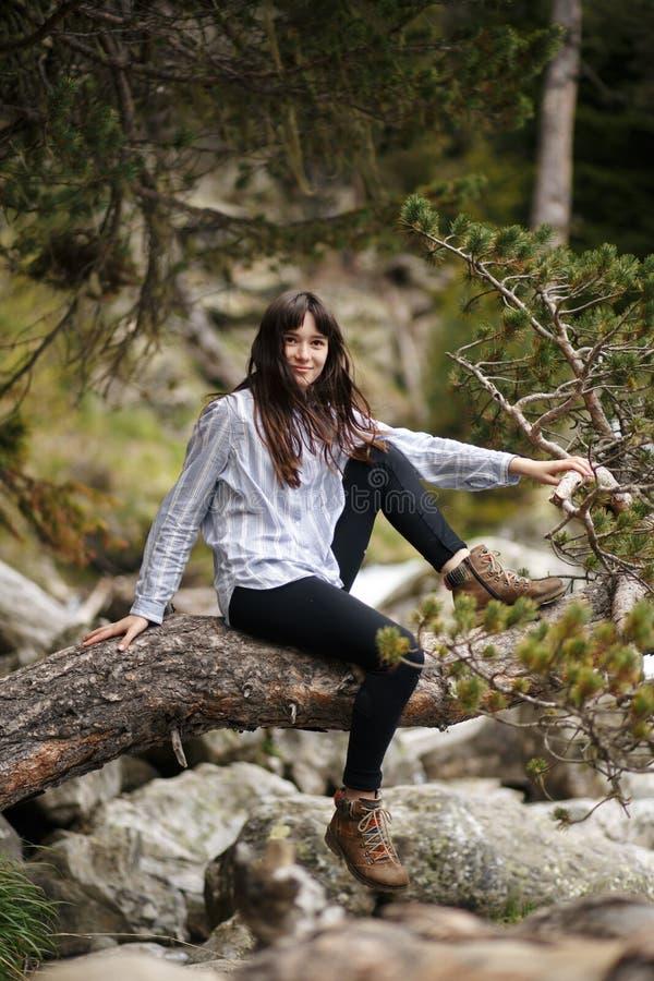 Ragazza dei pantaloni a vita bassa con lo zaino che gode del tramonto sulla montagna di punta Viaggiatore turistico sulla vista d fotografia stock