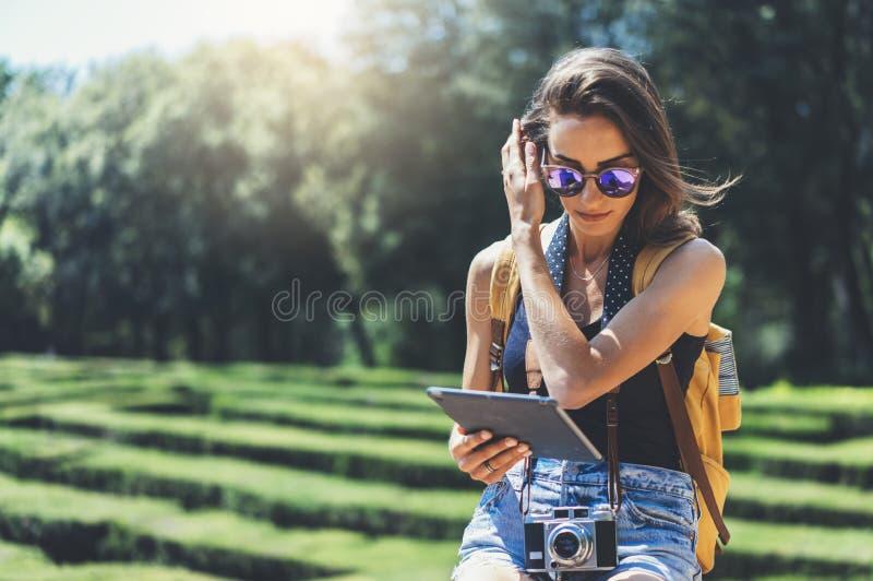 Ragazza dei pantaloni a vita bassa con lo zaino, gli occhiali da sole e la macchina fotografica d'annata della foto facendo uso d immagine stock libera da diritti