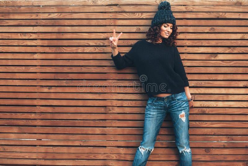Ragazza dei pantaloni a vita bassa sopra la parete di legno fotografia stock libera da diritti