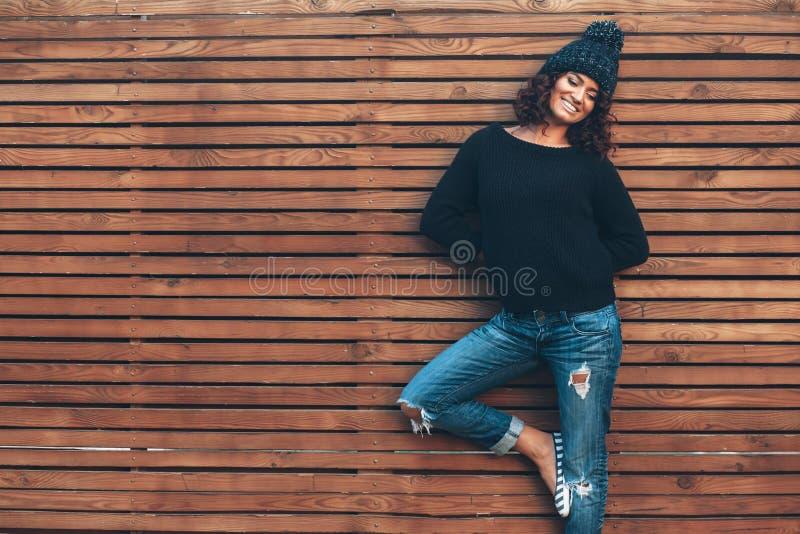 Ragazza dei pantaloni a vita bassa sopra la parete di legno immagini stock libere da diritti