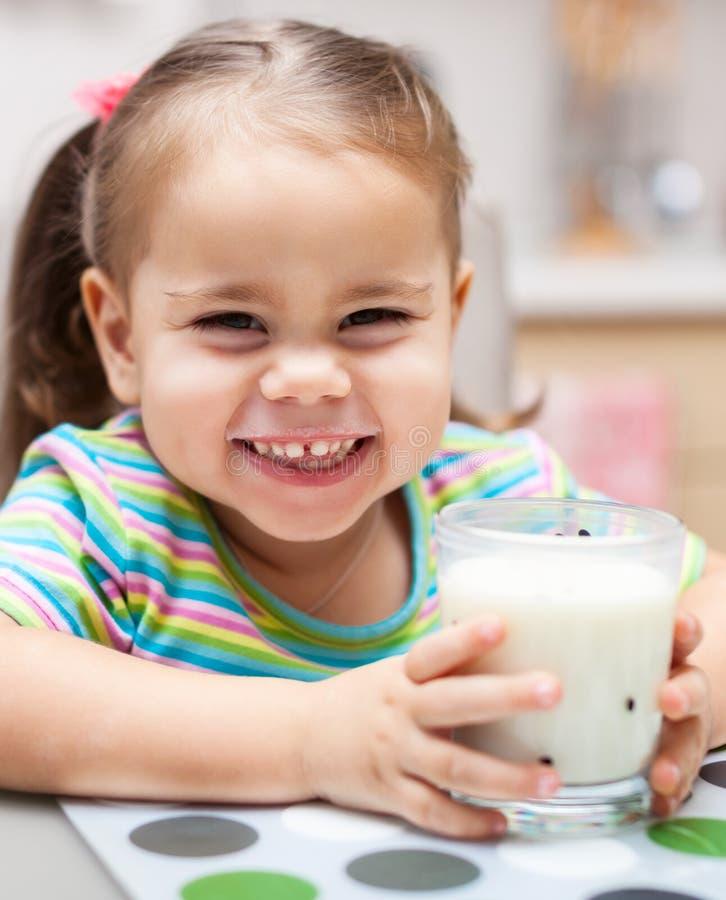 Ragazza del bambino che beve un bicchiere di latte a casa immagini stock