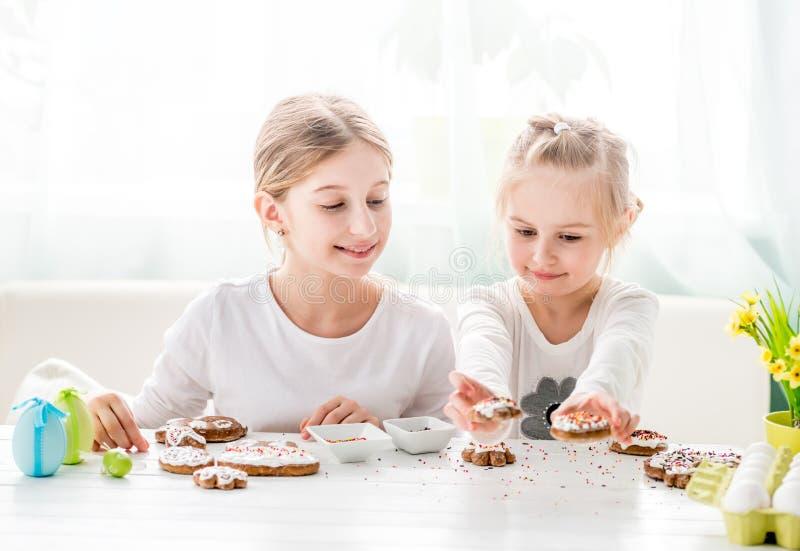 Ragazza del bambino che decora i biscotti di Pasqua immagini stock