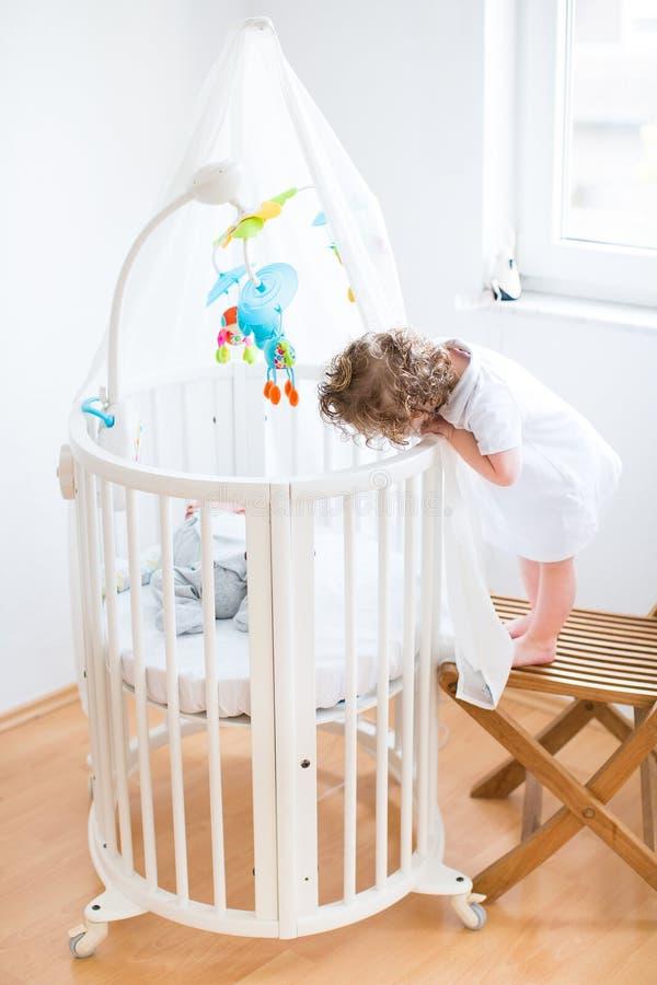 Ragazza del bambino che esamina suo fratello del neonato fotografie stock