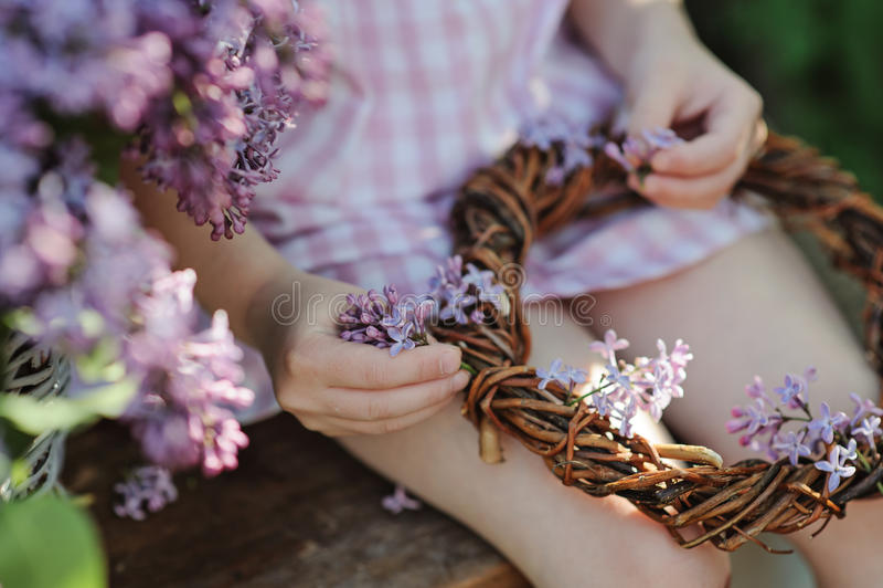 Ragazza del bambino che fa corona lilla nel giardino di fioritura di primavera fotografie stock libere da diritti