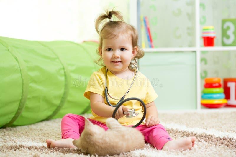 Ragazza del bambino che gioca al dottore With un gatto fotografia stock