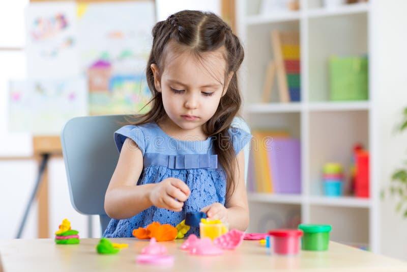 Ragazza del bambino che gioca con il plasticine a casa fotografia stock libera da diritti