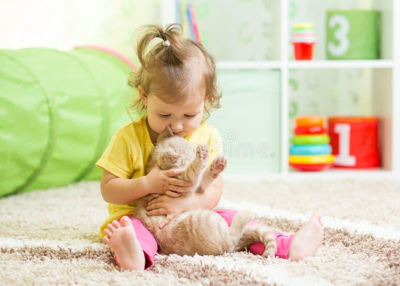 Ragazza del bambino che gioca con il suo gattino del gatto sul pavimento immagine stock libera da diritti