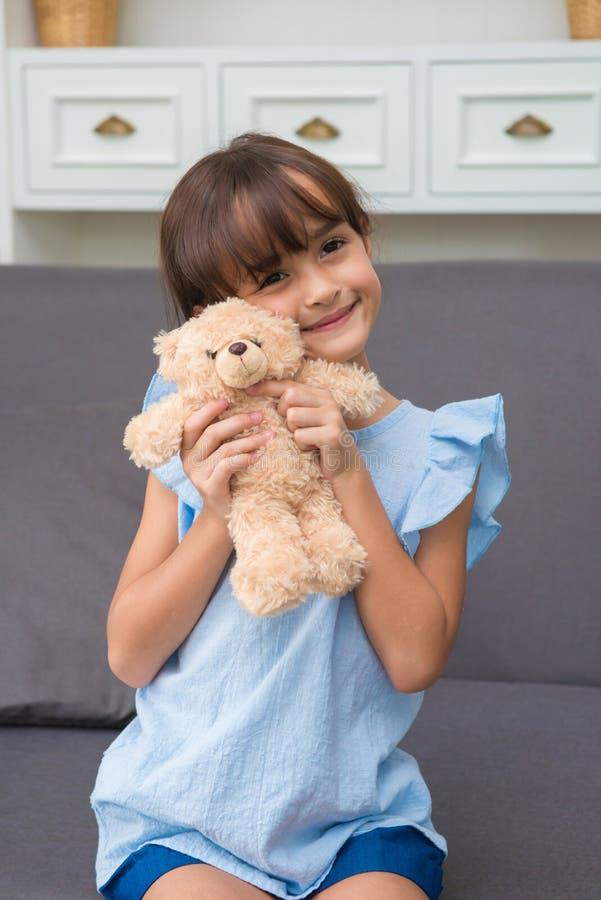 ragazza del bambino che gioca con Teddy Bear in salone a casa immagini stock