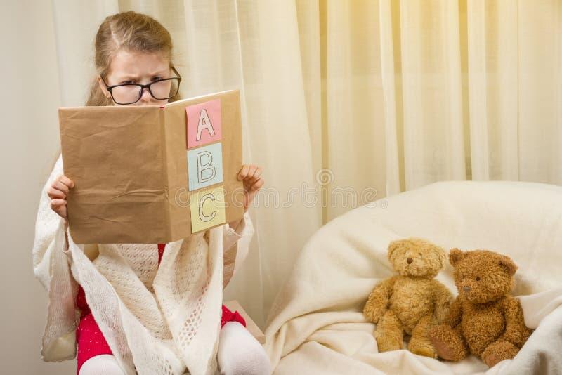 Ragazza del bambino che gioca un maestro di scuola con gli orsacchiotti a casa immagine stock libera da diritti
