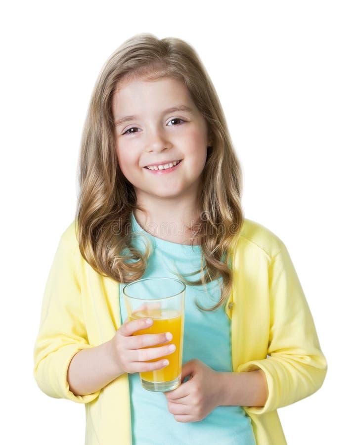 Ragazza del bambino che giudica succo d'arancia di vetro isolato su bianco immagini stock