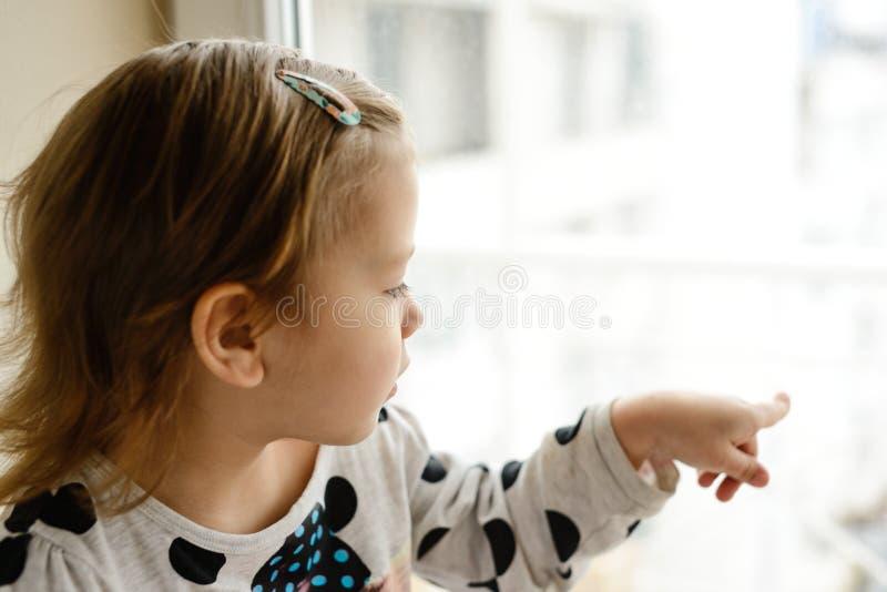 Ragazza del bambino che guarda nella finestra immagini stock libere da diritti
