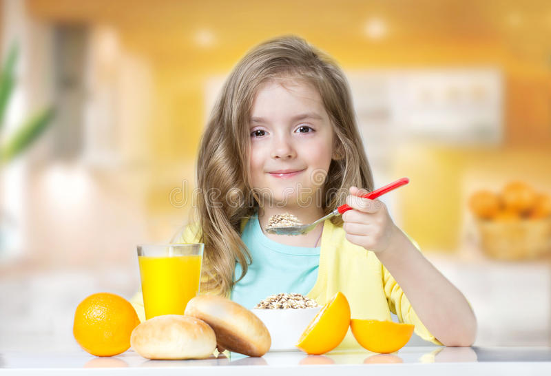 Ragazza del bambino che mangia al succo d'arancia del cereale della tavola all'interno fotografia stock libera da diritti