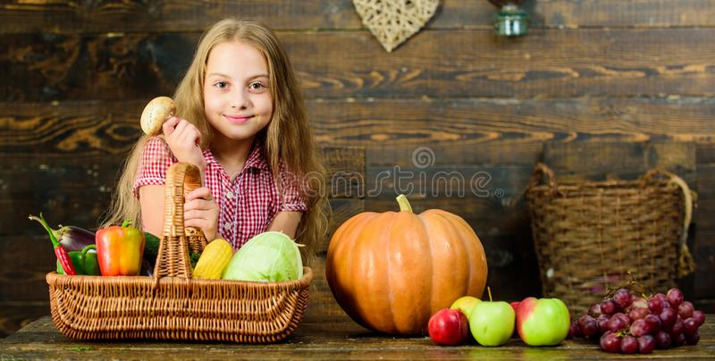 Ragazza del bambino che presenta raccolto del suo orto su fondo di legno Concetto di festival del raccolto Ragazza del bambino vi immagini stock