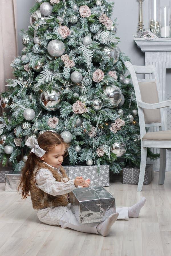Ragazza del bambino che si siede al pavimento vicino all'albero di Natale con il regalo di natale alle mani immagini stock