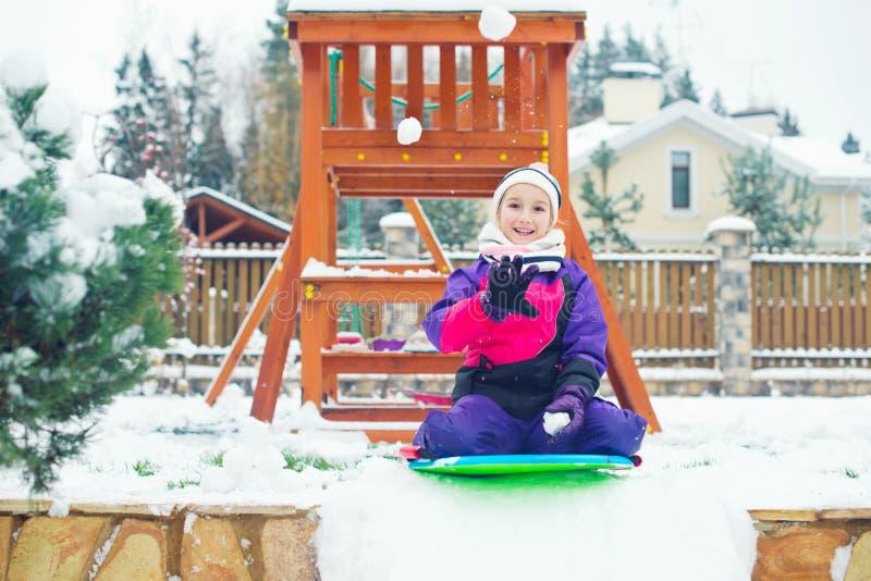 Ragazza del bambino che si siede sulla vanga da torba pronta a giocare lotta della palla di neve immagini stock