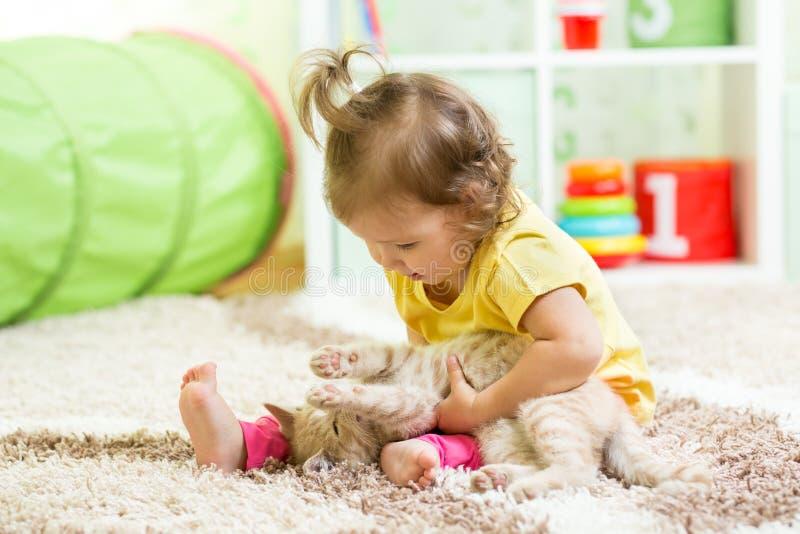 Ragazza del bambino che tiene il suo gattino del gatto sul pavimento immagine stock